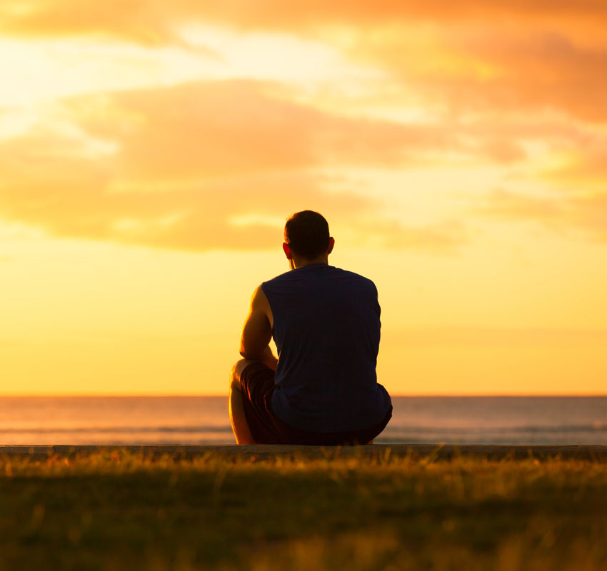 Young man sitting outdoors watching the sunset. Thinking and relaxing concept. - Image
